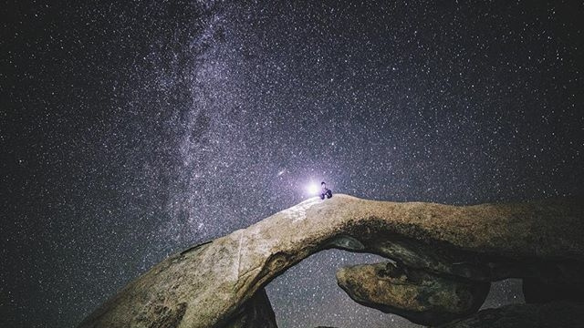 person sitting on rock communicating with stars