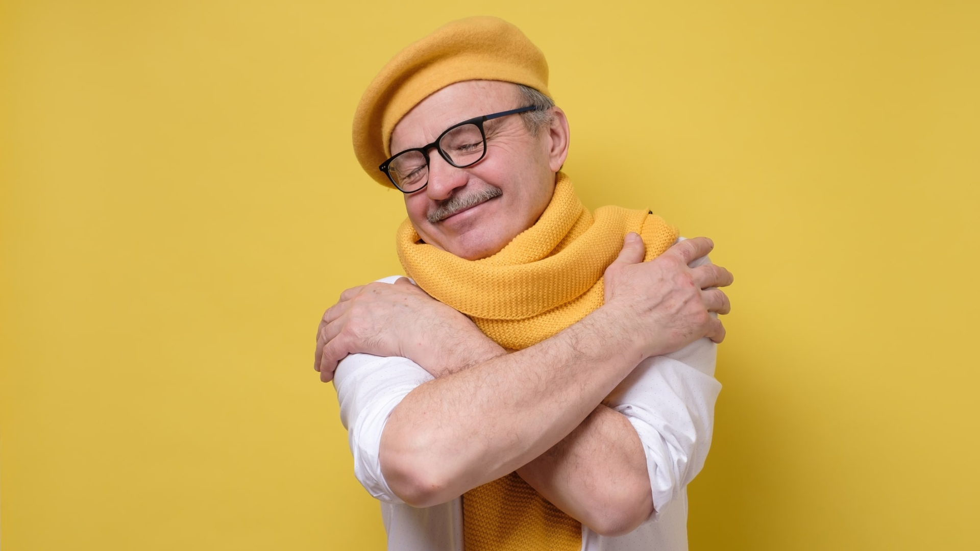 older man hugging himself happily wearing knitted hat and scarf